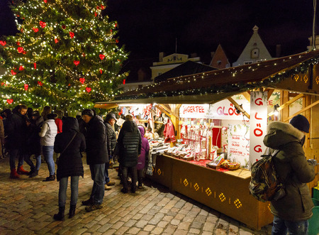 TALLINN, ESTONIA - DECEMBER 24, 2017: Tourists at Christmas market in Tallinn old town in Estonia on December 24, 2017