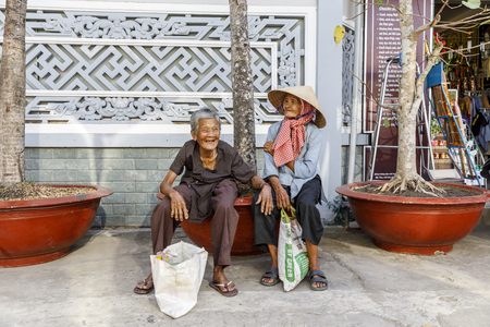MY THO, VIETNAM - FEBRUARY 24, 2018: Old Vietnamese women sit on a bench in My Tho, Vietnam