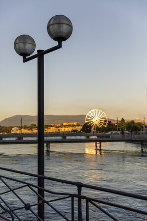 Round street lanterns by river, ferris wheel in sunlight at sunset in background in Geneva, Switzerland