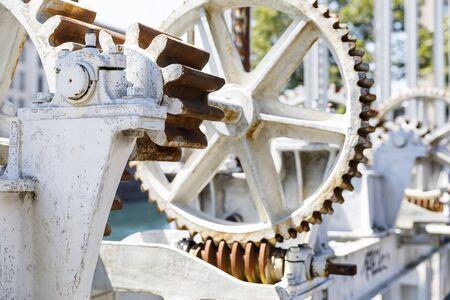 Heavy white gear wheels of machinery to open water gates at river Rhone in Geneva, Switzerland Фото со стока