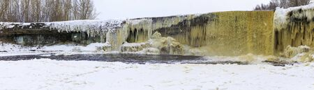 Panorama of partly frozen snowy and icy Jägala waterfall in Estonia