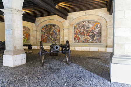 Old Arsenal cannon in front of mosaics in the old town of Geneva, Switzerland, each depicting a different monument in Genevas history