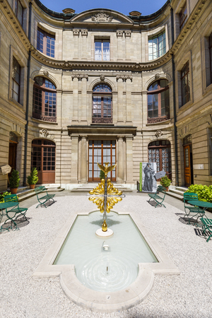 GENEVA, SWITZERLAND - JUNE 30, 2018: Courtyard with pool or fountain and benches surrounded by bulding walls in Geneva, Switzerland Sajtókép
