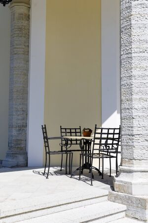 Cafe chairs and table against a building wall behind pillar