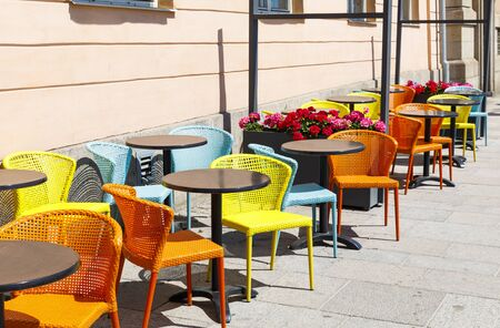 Colorful chairs with black tables in outdoor cafe on sunny summer day Stock fotó