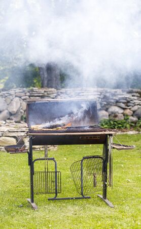 Smoking and flaming barbecue in a garden in summer Stock Photo