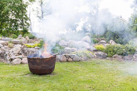 Smoking iron cauldron in a garden in summer
