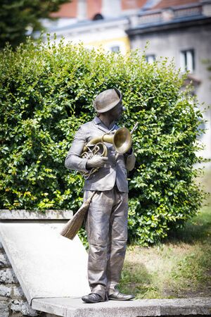 TALLINN, ESTONIA - JULY 05, 2019: Bronze colored living statue with a brush and music instrument stand on a wall in Tallinn, Estonia in July 2019