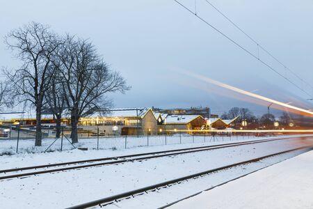 TALLINN, ESTONIA - DECEMBER 23, 2018: Rails and light strips of passing trains on snowy winter evening in Tallinn, Estonia on December 23, 2018