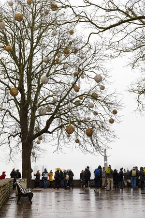 TALLINN, ESTONIA - DECEMBER 22, 2019: Decorated tree and tourists at viewpoint in the old town of Tallinn, Estonia in December 2019