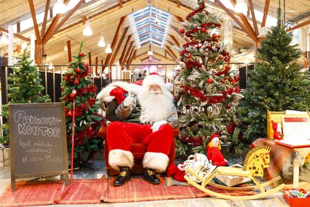 TALLINN, ESTONIA - DECEMBER 22, 2019: Santa claus sits between decorated fir trees in Balti Jaam market bulding in Tallinn Estonia in December 2019