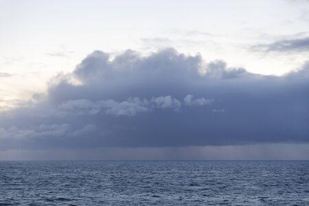 Dark storm clouds full of rain above the sea