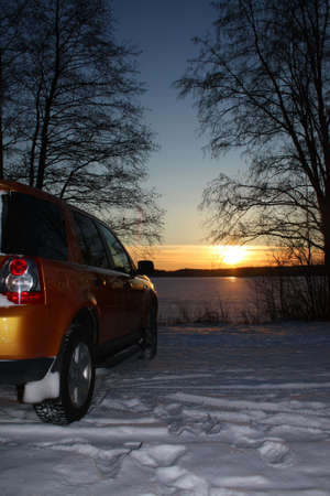 Car by frozen lake at sunset photo