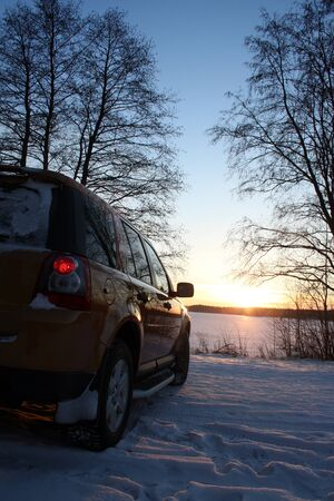 Car by frozen lake at sunset Stock Photo