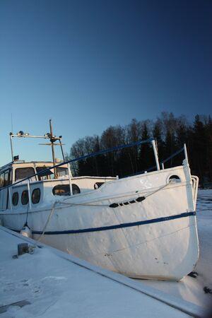 Winter boat in frozen lake Stock Photo