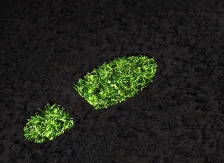 Green grass growing footprint on black asphalt