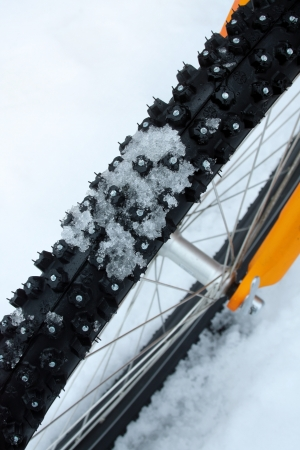 Studded bicycle tire with snow Stock Photo