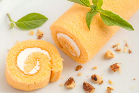Orange cake roll on a plate photo