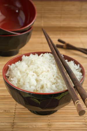 White steamed rice in a bowl with chopsticks Stock Photo