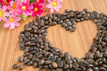 scattered in heart shaped: Heart shape made from coffee beans on wooden background Stock Photo