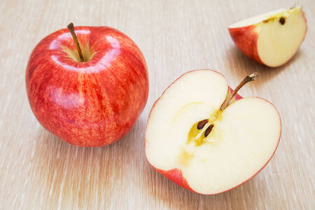 Fresh red apples and slices on wooden background photo