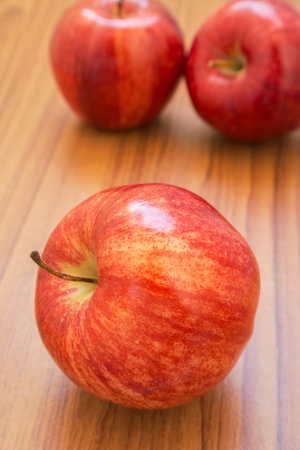 Fresh red apples on wooden background photo