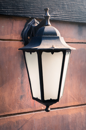 Antique lamp on the stone wall photo