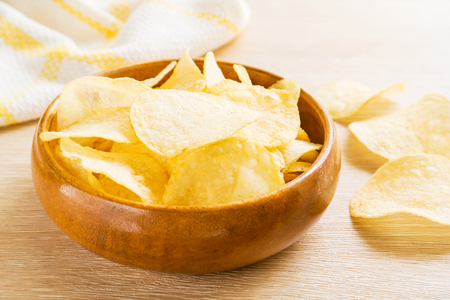 Potato chips in wooden bowl on table