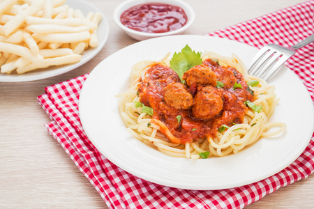Spaghetti with meatballs in tomato sauce and french fries photo