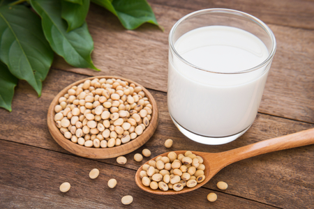 Soja-melk en soja bonen op houten achtergrond Stockfoto