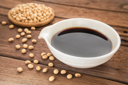 Soy sauce and soy bean on wooden background Stock Photo