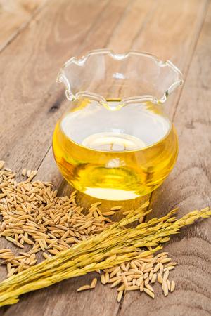 arroz: Aceite de salvado de arroz en botella de vidrio y el arroz sin moler en el fondo de madera Foto de archivo