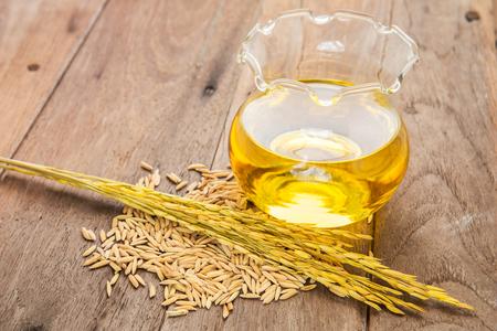 Rijst zemelen olie in de fles glas en unmilled rijst op houten achtergrond Stockfoto