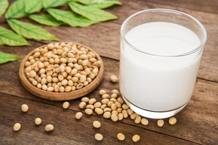 leche de soya: La leche de soya y frijol de soya en la mesa de madera Foto de archivo