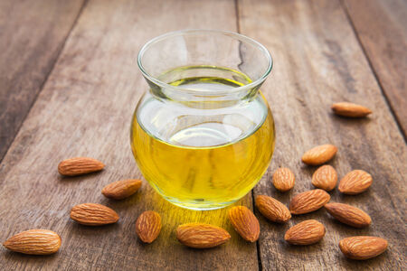 Almond oil in glass bottle and almonds photo