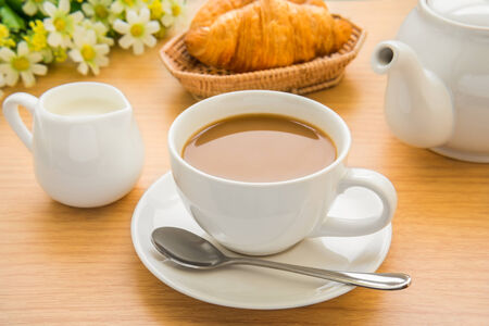 Coffee cup, milk and croissant on wooden table photo