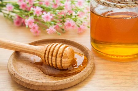blossom honey: Honey dipper on wooden plate and jar Stock Photo