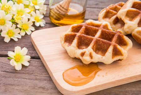 honey cake: Waffles with honey on wooden plate