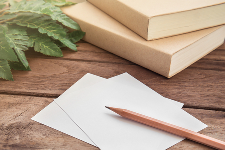 Pencil with paper and book on wooden table