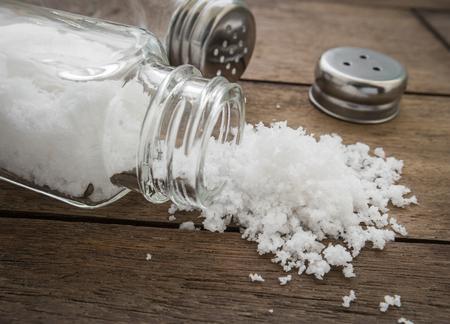 Gemorst zout met zout shaker op houten achtergrond