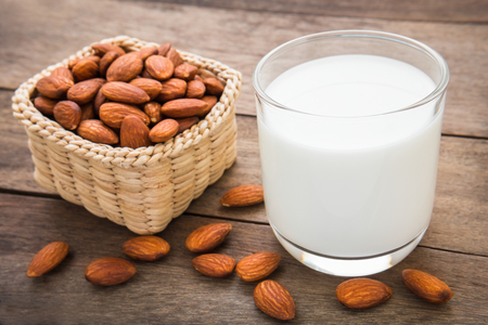 almond: Almond milk in glass with almonds on wooden table
