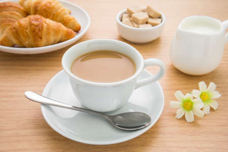 Cup of coffee, croissants, milk jug and sugar on table photo