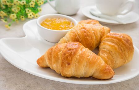 Croissants with jam on plate and coffee cup photo