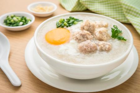 Congee con carne de cerdo picada y huevo en un tazón