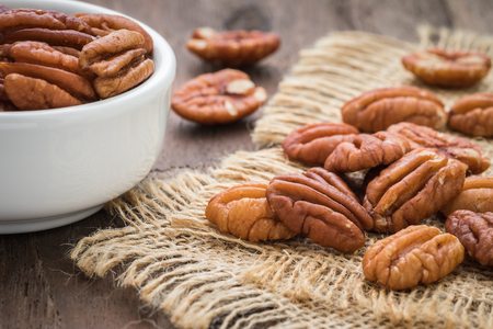 Pecan nuts on sackcloth and bowl