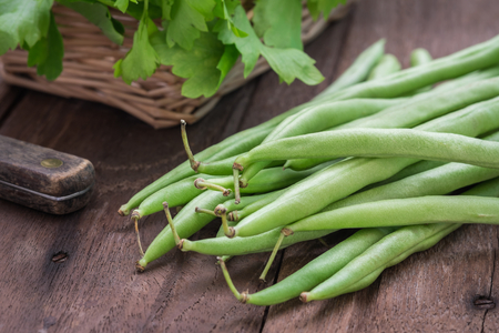 Green beans on wooden table Stock Photo