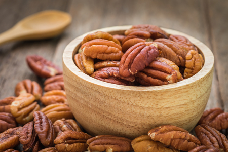Pecan nuts in wooden bowl Фото со стока