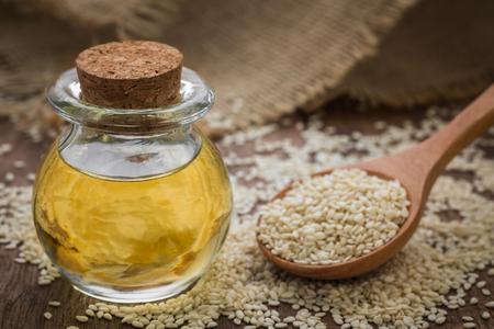 Olio di sesamo in vaso di vetro e semi di sesamo il cucchiaio di legno
