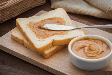 mantequilla: S�ndwich de mantequilla de man� sobre tabla de madera