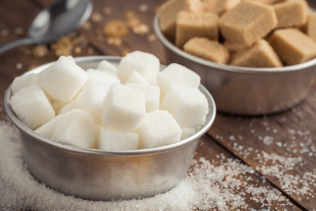 sugar cubes: White sugar and brown sugar in bowl on wooden table Stock Photo